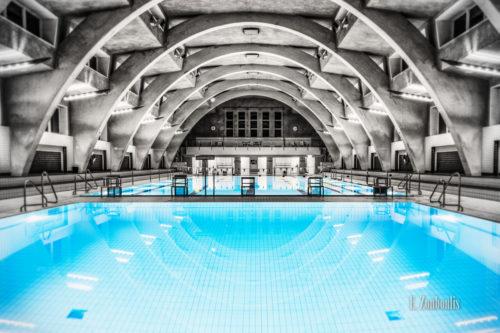 Innenaufnahme des Heslacher Hallenbads in Schwarzweiss mit blauem Wasser