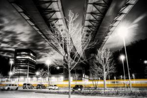 Unter der Brücke in Südheim. Bild in Schwarzweiss mit einer vorbeirauschenden Strassenbahn in gelber Farbe