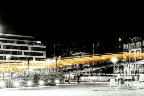 Der Lichtschweif einer Zahnradbahn am Marienplatz. Bild in Schwarzweiss mit gelbem Lichtschweif.