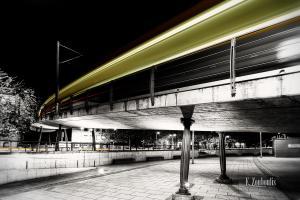 Bild am Marienplatz in Schwarzweiss mit gelbem Lichtschweif der vorbeiziehenden Zahnradbahn