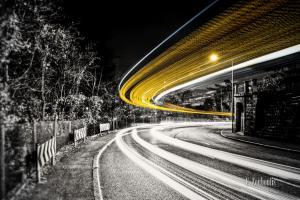 Bild in Schwarzweiss am Killesberg mit gelbem Lichtschweif eines vorbeiziehenden Busses.