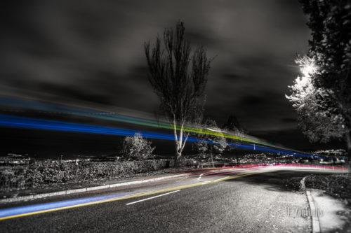 Bild in Schwarzweiss mit farbigem Lichtschweif des vorbeiziehenden Verkehrs.