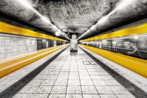 Bild in Schwarzweiss und zwei gelben ein- und ausfahrenden Strassenbahnen