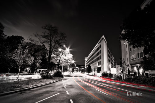 Schwarzweiss-Aufnahme mit roten Lichtschweifen in Richtung der Stuttgarter Innenstadt