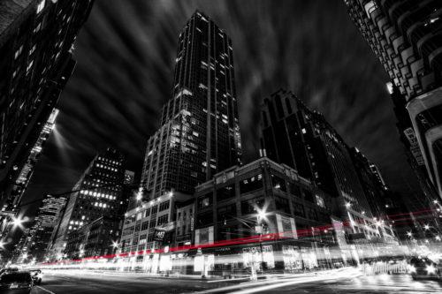 Schwarzweiss-Aufnahme in New York City. Im Hintergrund die Hochhäuser und im Vordergrund der Verkehr, der als roter Lichtschweif zu erkennen ist