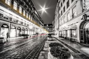 Schwarzweiss-Aufnahme in der Perusastraße in München. Farbige Lichtschweife in Gelb und Rot entlang der Schienen