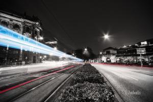 Schwarzweiss-Aufnahme am Lenbachplatz in München. Rote und blaue Lichtschweife sind zu sehen.