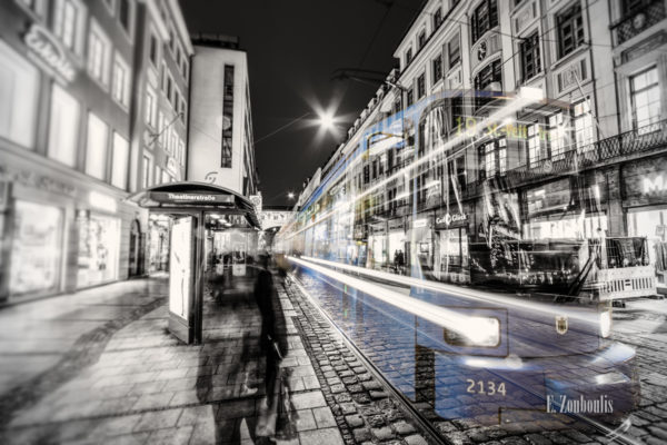 Bild in Schwarzweiss mit blau einfahrender Tram an der Theatinerstraße.