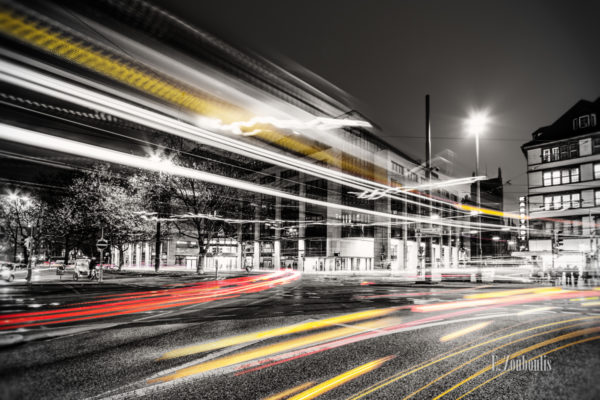 Schwarzweiss-Aufnahme des vorbeiziehenden Verkehrs mit farbigem Lichtschweif am Karlsplatz