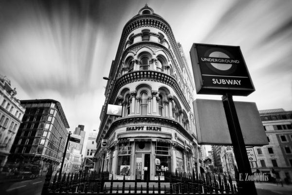 Schwarzweiss-Aufnahme in London mit einem Subway-Schild im Vordergrund, einem Eckhaus in der Mitte und vorbeiziehenden Wolken.