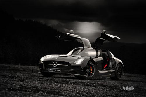 Schwarzer Mercedes SLS AMG Black Series mit geöffneten Flügeltüren am Schwarzwald. Bild in Schwarzweiss mit farbigen Elementen.
