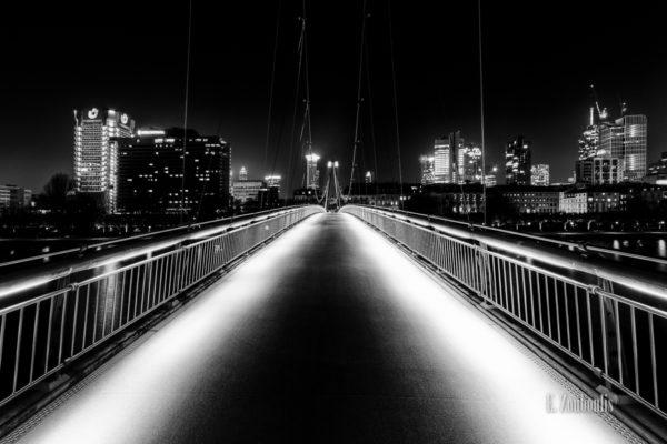 Schwarzweiss--Aufnahme auf der Brücke am Schaumainkai in Frankfurt und der Frankfurter Skyline im Hintergrund