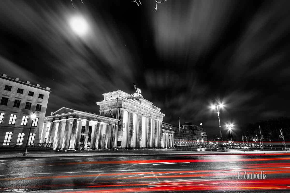 Langzeitbelichtung am Brandenburger Tor in Berlin. Schwarzweiss mit roten Lichtschweifen, die den Verkehr erkennen lassen