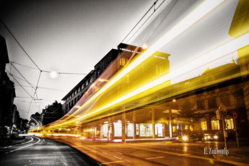 Schwarzweiss-Aufnahme am Generationenhaus in Heslach mit einer vorbeiziehenden Strassenbahn als Lichtschweif in gelb