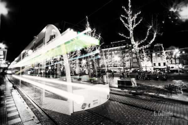 Schwarzweiss-Aufnahme einer Tram mit farbigem Lichtschweif in Amsterdam