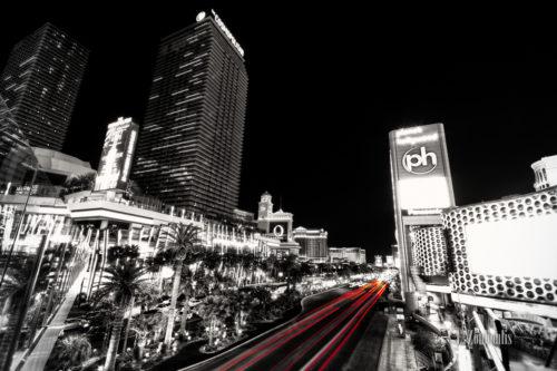 Schwarzweiss-Aufnahme am Las Vegas Strip mit roten Lichtschweifen, die den Verkehr an der Hauptader der Stadt erkennen lassen. Rechts das Planet Hollywood Casino und auf der Linken seite das Cosmopolitan vor dem Bellagio Casino