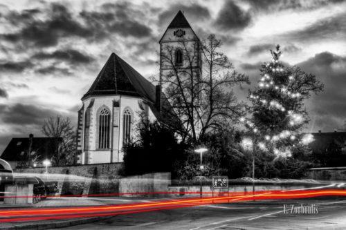 Schwarzweiss-Aufnahme zur Weihnachtszeit in Gärtringen mit der St. Veit Kirche im Hintergrund und einem roten Lichtschweif im Vordergrund
