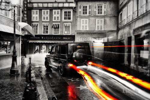 Schwarzweiss-Aufnahme einer vorbeirauschenden Mercedes AMG G-Klasse in den Straßen des Europaparks. Der G63 hinterlässt einen farbigen Lichtschweif