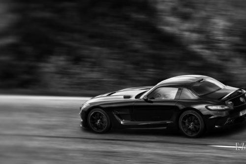 Schwarzweiss-Aufnahme eines vorbeiflitzenden Mercedes Benz SLS AMG Black Series