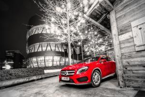 Schwarzweiss-Aufnahme eines roten Mercedes Benz GLA vor dem Mercedes Benz Museum