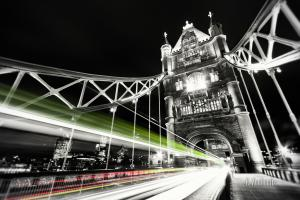 Schwarzweiss-Aufnahme mit farbigen Lichtschweifen, die den Verkehr an der Tower Bridge in London erkennen lassen
