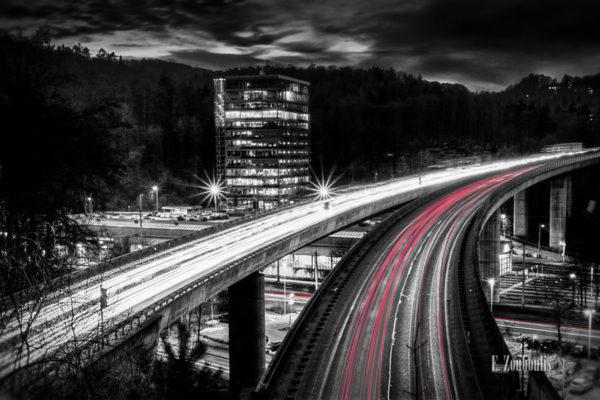 Schwarzweiss-Aufnahme mit roten Lichtschweifen, die den Verkehr kennzeichnen. Nachtaufnahme über der B14