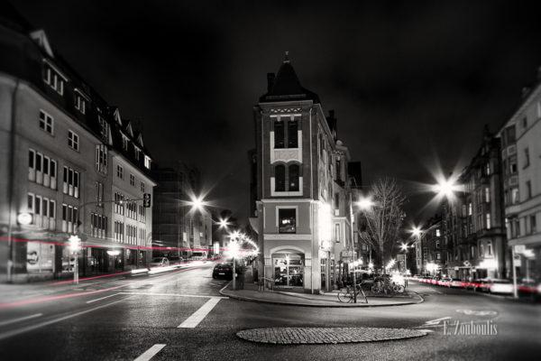 Schwarzweiss-Aufnahme am Marienplatz mit roten Lichtschweifen, die den Verkehr sichtbar machen