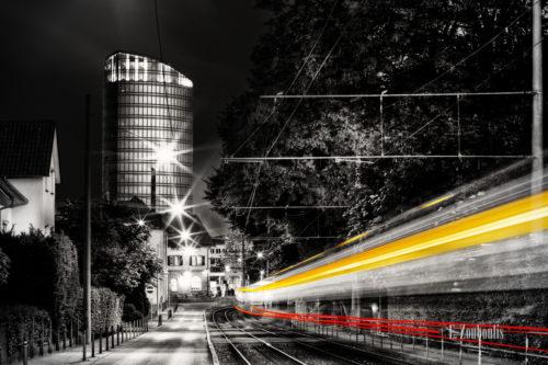 Schwarzweiss-Aufnahme mit roten und gelben Lichtschweifen einer vorbeirauschenden Straßenbahn in Stuttgart Vaihingen