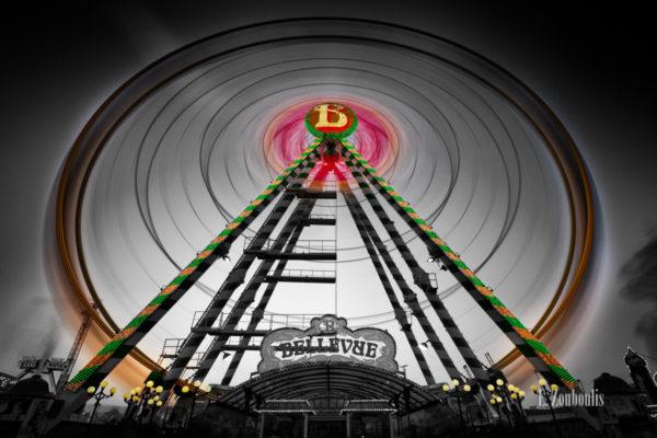 Schwarzweiss-Aufnahme mit farbigem Riesenrad zum Volksfest