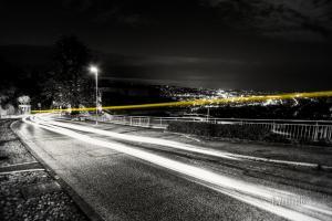 Schwarzweiss-Aufnahme an der Alten Weinsteige in Stuttgart mit einem gelben Lichtschweif eines Taxis