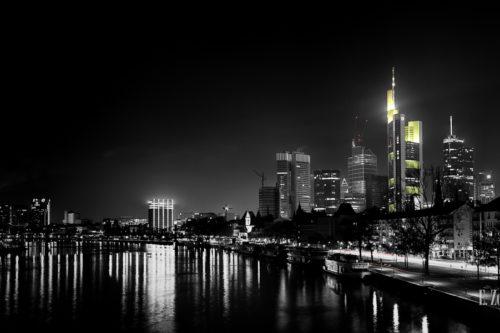 Eine Panorama Aufnahme von Frankfurt bei Nacht mit den Hochhäusern des Finanzdistrikts im Hintergrund. Schwarzweiß mit gelben und roten Elementen