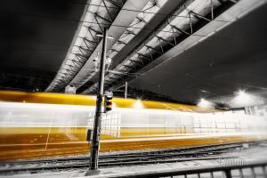 Schwarzweiss-Aufnahme unter der Brücke der B14 mit einer Straßenbahn, die in Form eines gelben Lichtschweifs aus dem Depot strömt