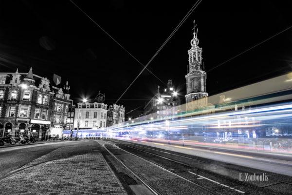 Schwarzweiss-Aufnahme am Muntplein, Amsterdam mit einer vorbeirauschenden Tram in Form eines farbigen Lichtschweifs