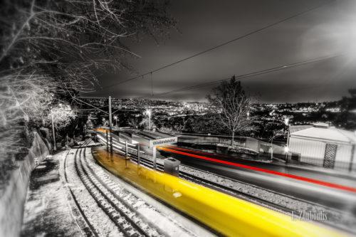 Schwarzweiss-Aufnahme an der Wielandshöhe, Stuttgart mit der Zahnradbahn in Form eines gelben Lichtschweifs.