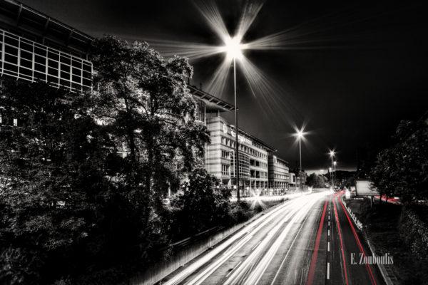 Schwarzweiss-Aufnahme an der B14 in Stuttgart. Rote und weiße Lichtschweife kennzeichnen den Verkehr bei Nacht