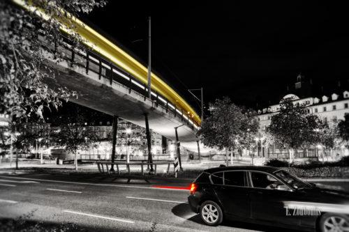 Schwarzweiss-Aufnahme am Marienplatz mit gelbem Lichtschweif der Zahradbahn und einem roten Lichtschweif eines Fahrzeugs im Vordergrund