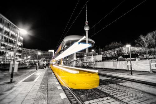 Schwarzweiss-Aufnahme einer einfahrenden Straßenbahn am Alexanderplatz in Berlin. Schwarzweiss mit farbigem Lichtschweif, der die Straßenbahn erkennen lässt