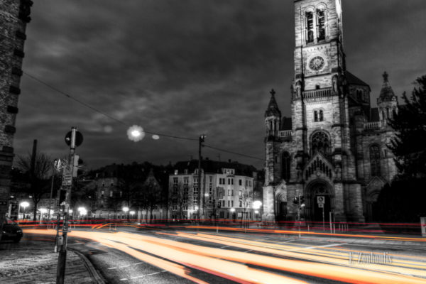 Schwarzweiss-Aufnahme an der Matthäuskirche in Stuttgart Heslach mit farbigen Lichtschweifen, die den Verkehr sichtbar machen