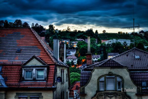 HDR-Aufnahme zur blauen Stunde in Stuttgart Heslach. Zu sehen sind die Dächer der Gebäude und auf dem Hügel rechts ist die Wilhelm-Hauff Schule