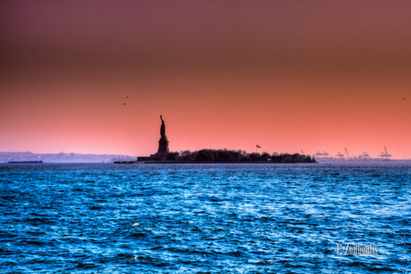 Aufnahme an der Freiheitsstatue in New York. Im Vordergrund blaues Wasser, in der Mitte des Bildes die Freiheitsstatue und im Hintergrund Industrieanlagen und Hubschrauber
