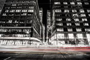 Schwarzweiss-Aufnahme in New York City. Im Hintergrund die Hochhäuser und im Vordergrund der Verkehr, der als farbiger Lichtschweif zu erkennen ist