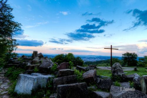 Aufnahme zum Sonnenuntergang auf dem Birkenkopf in Stuttgart. Im Vordergrund und links die Steine, die als Mahnmal gelten, rechts im Bild das große Kreuz und im Hintergrund Stuttgart und der Fernsehturm