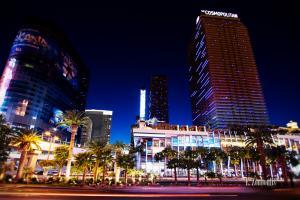 Aufnahme zur späten blauen Stunde auf dem Las Vegas Strip in Las Vegas, Nevada, USA. Im Vordergrund sind die Straße und Palmen zu sehen und im Hintergrund das Cosmopolitan Hotel und Casino