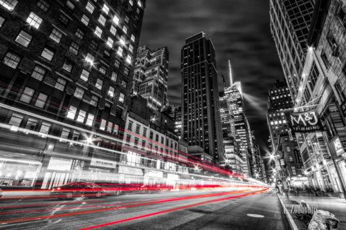 Schwarzweiss-Aufnahme in New York City. Rote Lichtschweife kennzeichnen den Verkehr. Auf dem Gehweg wurde der Müll abgeladen.