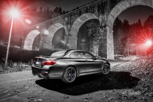 Ein grauer BMW M4 an einem Aquädukt bei Freudenstadt. Schwarzweiss mit roten und blauen Elementen