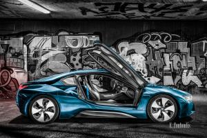 Schwarzweiss-Aufnahme mit einem blauen BMW i8 mit geöffneten Flügeltüren vor einer Graffiti Wand
