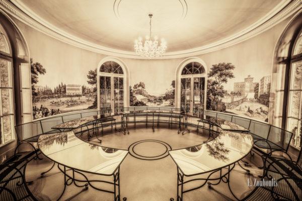 Sepia Aufnahme in der Villa Schwalbenhof. Glastische und Sitzbänke im Kreis unterhalb eines Kronleuchters und schönen Wandbildern
