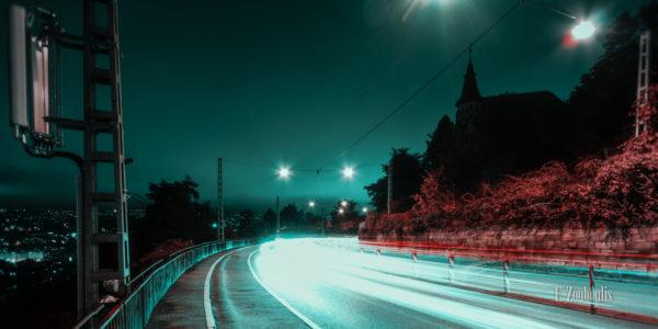 Nachtaufnahme an der Weinsteige in Stuttgart. Lichtschweif des Verkehrs in einer grün/blau roter Stimmung