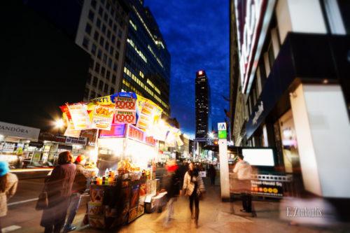 Aufnahme zur blauen Stunde in New York City. Links im Vordergrund ein Hot Dog Stand und viele Passanten, die zu jeder Zeit in NY unterwegs sind