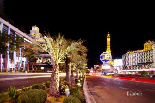 Nachtaufnahme in Las Vegas. Rechts im Bild das Planet Hollywood vor dem Paris Hotel und Casino und auf der linken Seite hinter den Palmen das Bellagio
